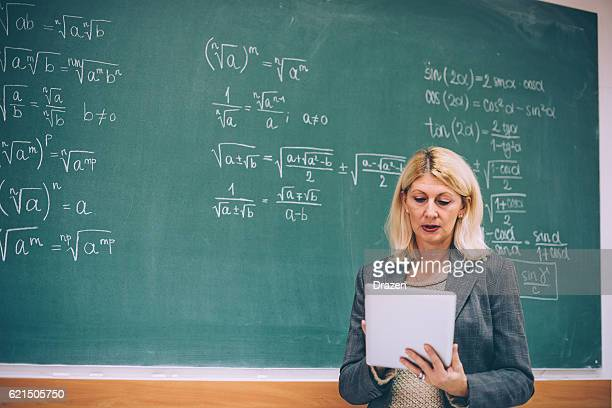Female math professor in classroom with digital tablet