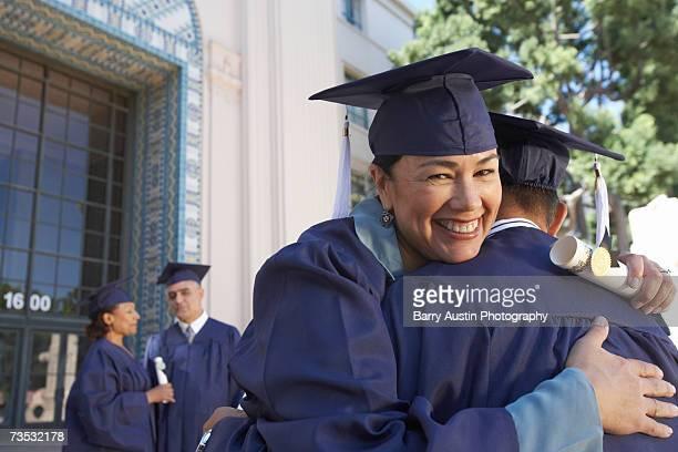 Female mature graduate student embracing colleague, outdoors, portrait