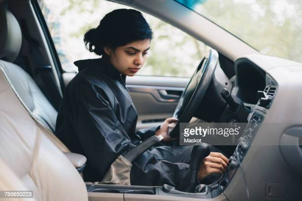 Female mechanic adjusting knob on dashboard in car
