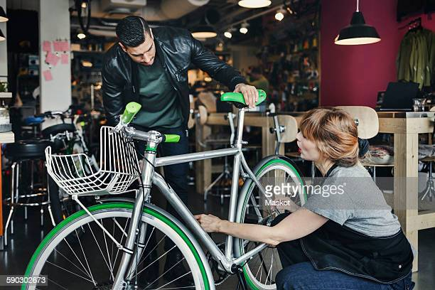 Female mechanic analyzing bicycle while talking to customer in repair shop