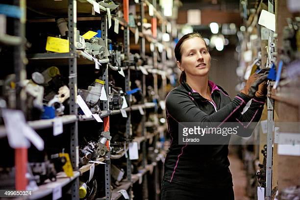 female mechanic at workshop storage - junkyard stock photos and pictures