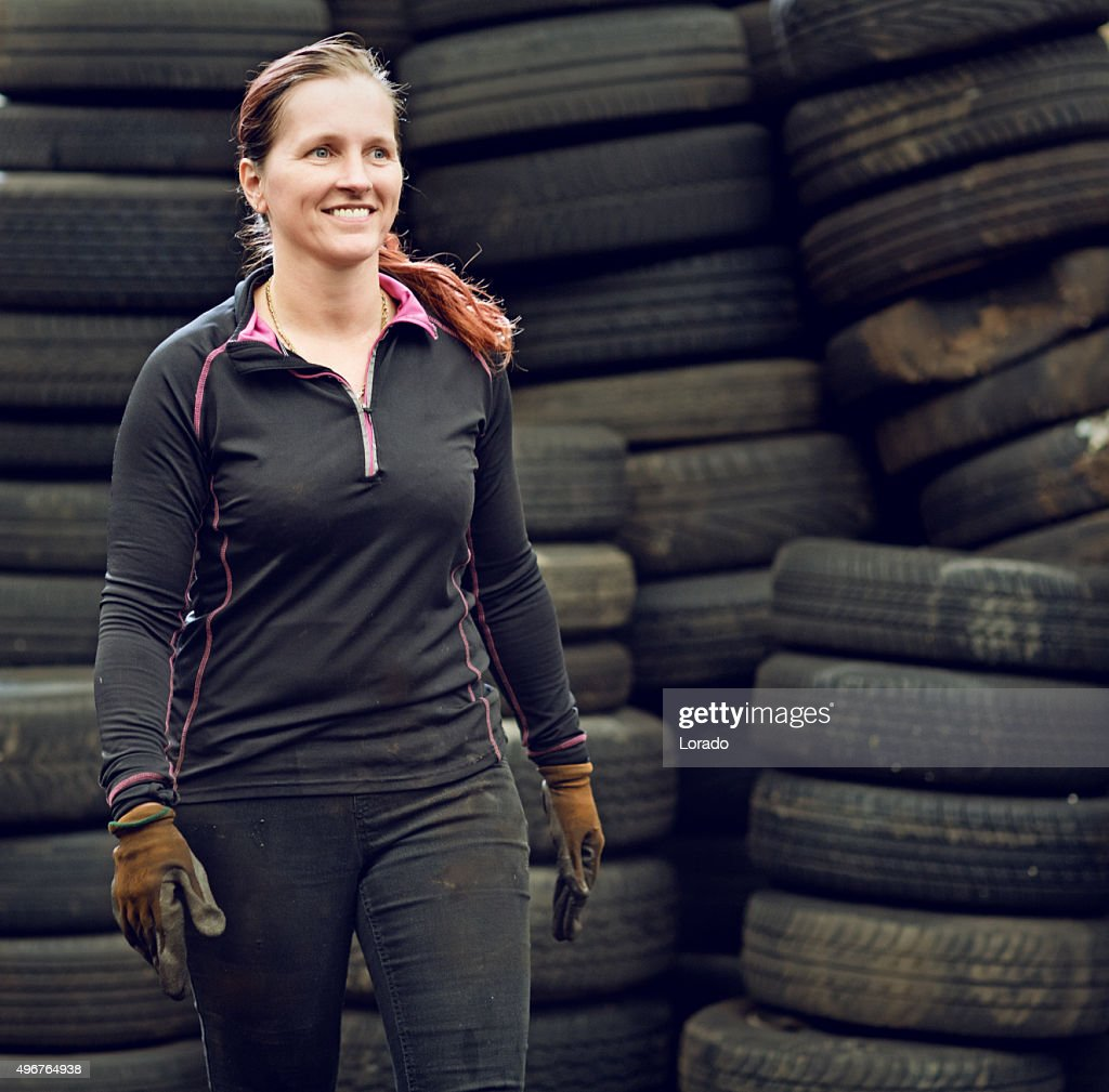 female mechanic carrying tires : Stock Photo