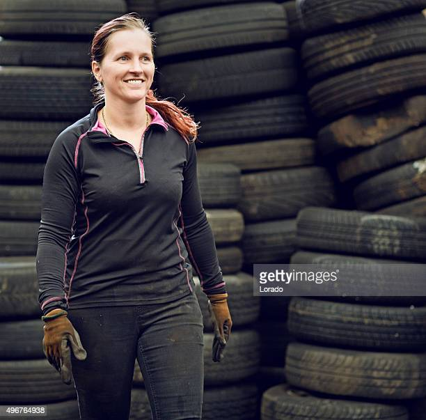 female mechanic carrying tires - junkyard stock photos and pictures