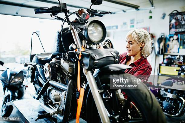 Female mechanic changing oil on motorcycle