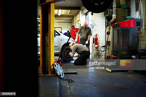 Female mechanic changing tires in garage