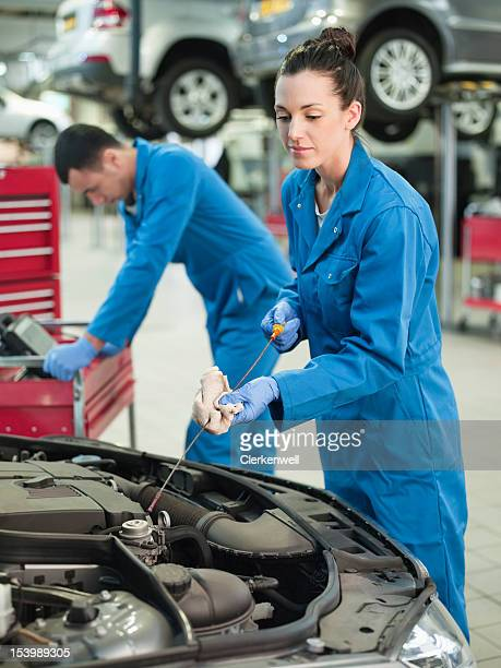 female mechanic checking oil with dip stick in auto repair shop - oil change stock pictures, royalty-free photos & images
