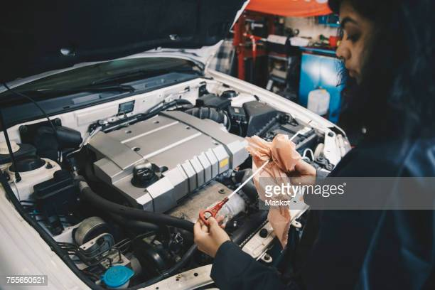 Female mechanic cleaning dipstick with paper at auto repair shop