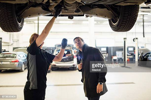 Female mechanic discussing with client under car at repair shop