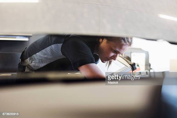 Female mechanic examining car seen through windshield at shop