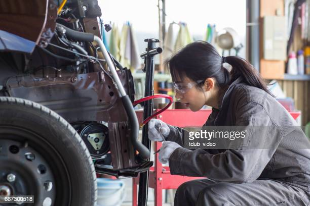 female mechanic fixing a damaged car in an auto repair shop - tdub_video stock pictures, royalty-free photos & images