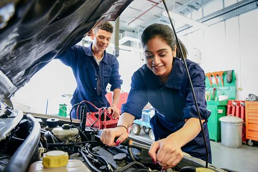 Female mechanic fixing car, young man watching 914314364