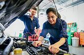 Female mechanic fixing car, young man watching