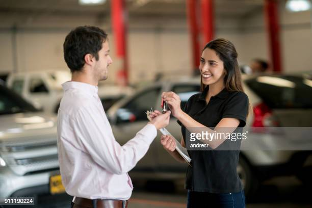 Female mechanic giving car keys to a happy customer at an auto repair shop