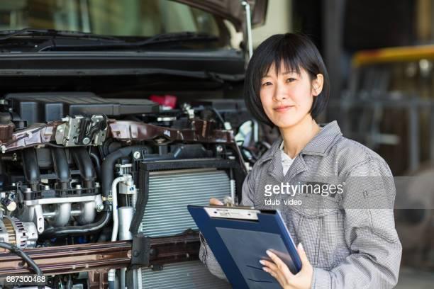 自動修理ガレージに破損した車を検査女性メカニック - オーバーオール ストックフォトと画像