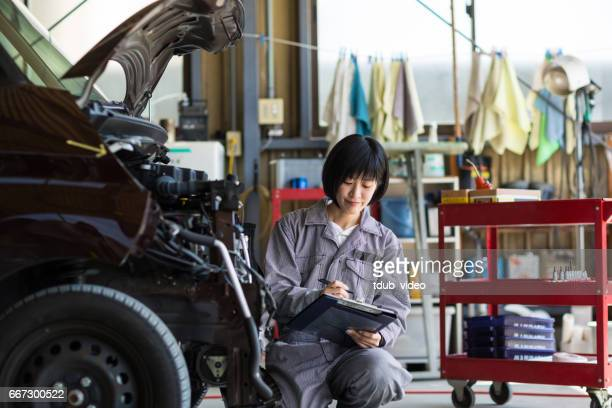 Female mechanic inspecting a damaged car in an auto repair garage