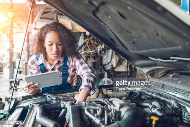 female mechanic inspecting a damaged car with digital tablet in an auto repair garage - improvement stock pictures, royalty-free photos & images