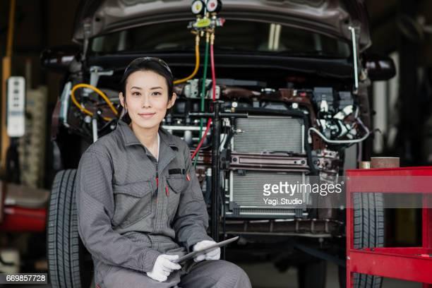 自動でデジタル タブレットで破損した車を検査女性メカニック修理ガレージ - 交通事故 ストックフォトと画像