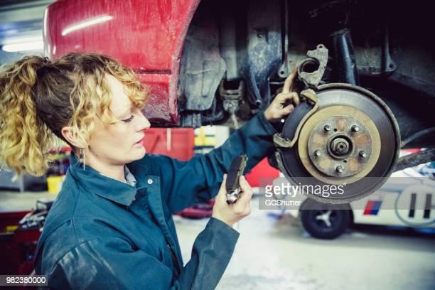 Female mechanic inspecting the brake pad