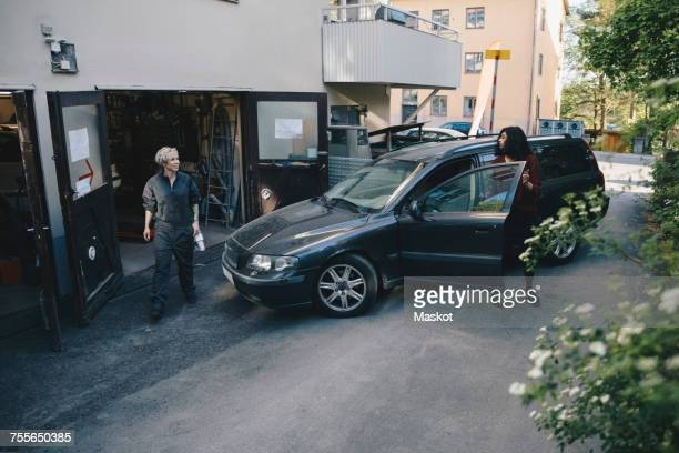 female mechanic looking at customer opening car door outside auto repair shop - auto repair shop exterior stock pictures, royalty-free photos & images