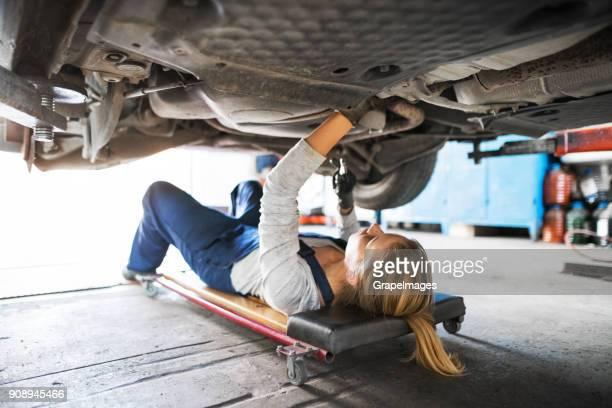 female mechanic repairing a car in a garage. - sotto foto e immagini stock