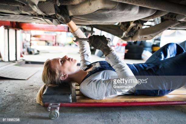 feminino mecânico consertando um carro em uma garagem. - igualdade - fotografias e filmes do acervo