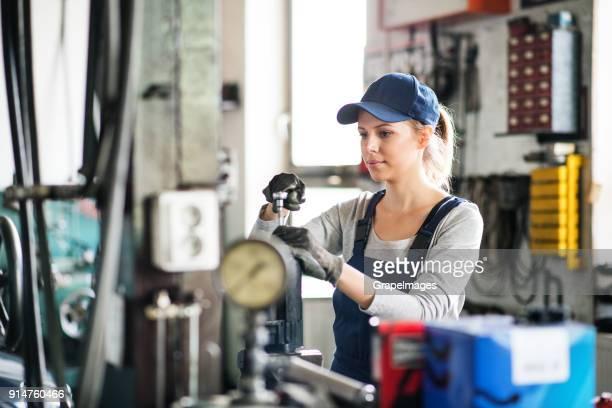 weibliche mechaniker repariert ein auto in einer garage. - handwerker stock-fotos und bilder