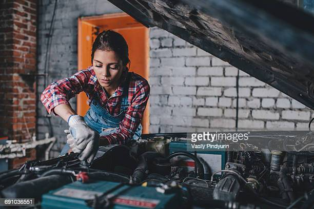 female mechanic repairing car engine at garage - mechanic stock pictures, royalty-free photos & images