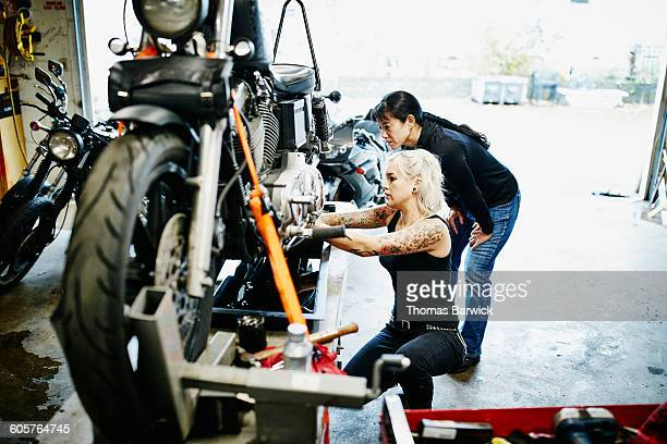 female mechanic teaching friend how to change oil - leanincollection stock pictures, royalty-free photos & images