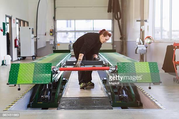 Female mechanic using hydraulic lift in auto repair shop