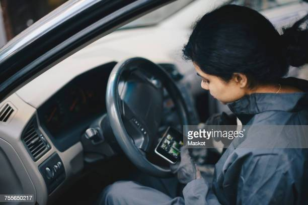 Female mechanic using mobile phone while sitting in car