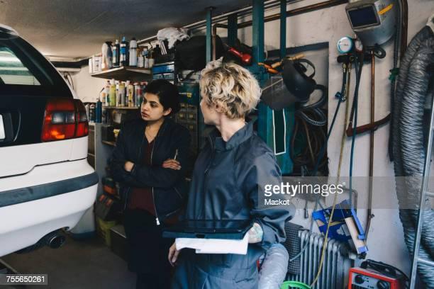 Female mechanic with customer examining car at auto repair shop