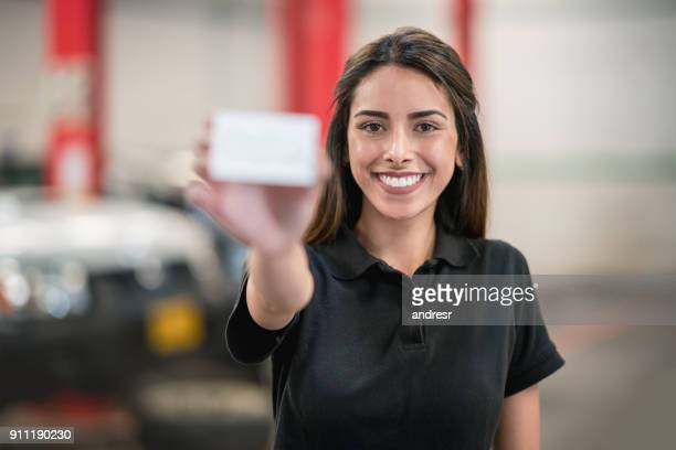 female mechanic working at a garage holding a business card - contact us stock pictures, royalty-free photos & images