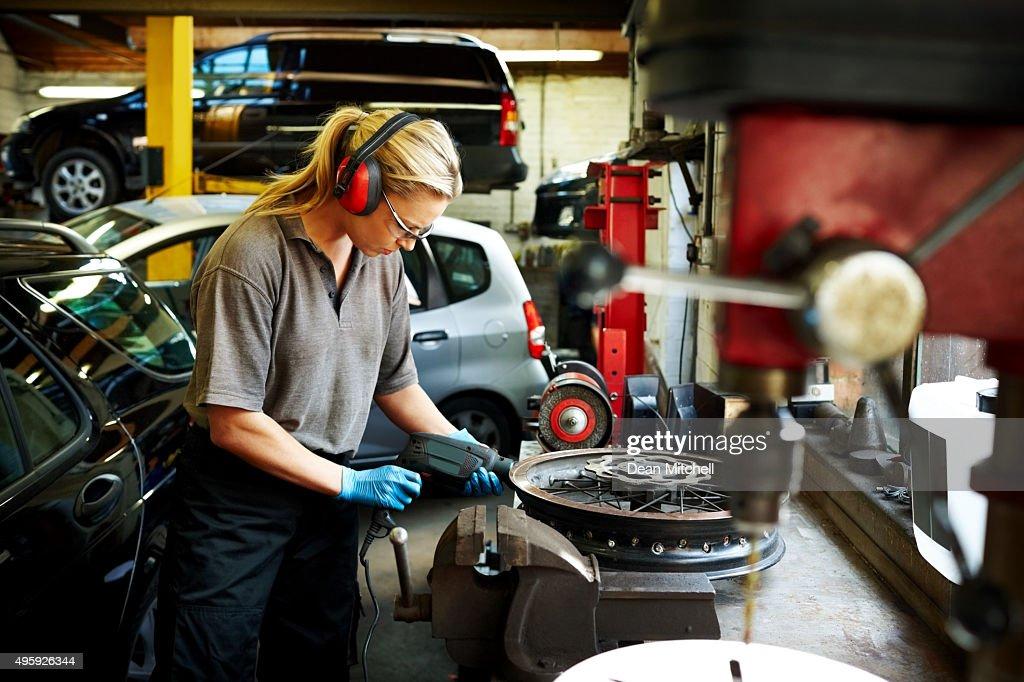 Female mechanic working in auto garage : Stock Photo