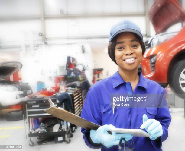 female mechanic working in garage - paycheck protection stock pictures, royalty-free photos & images