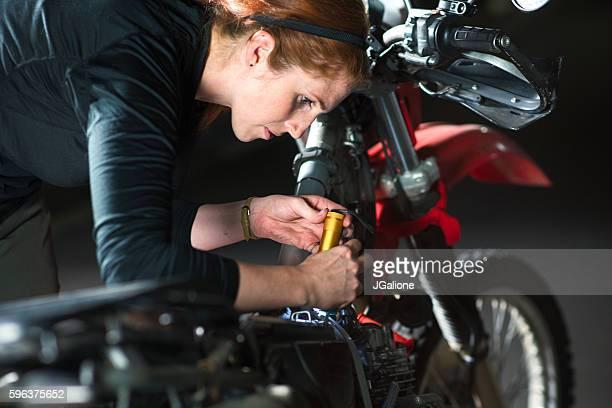 Female mechanic working on a motorbike