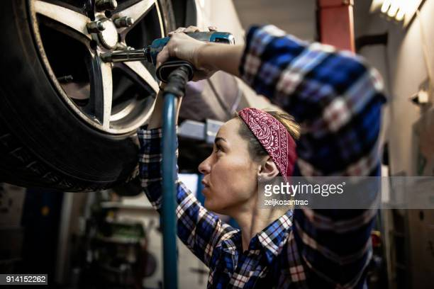 female mechanic working on car tyre service - adjusting stock pictures, royalty-free photos & images