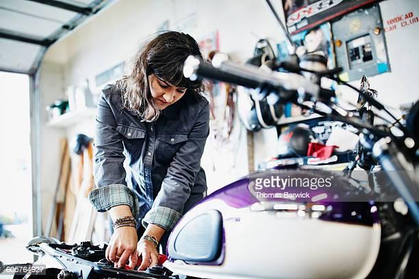 Female mechanic working on motorcycle in garage