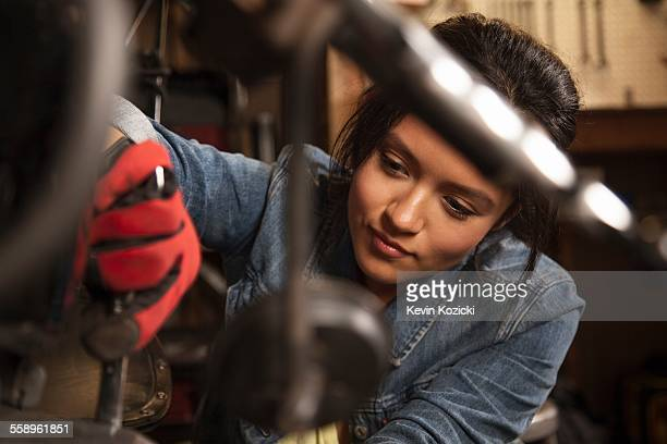female mechanic working on motorcycle in workshop - differential focus stock pictures, royalty-free photos & images