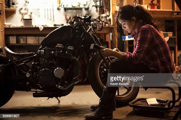 Female mechanic working on motorcycle in workshop