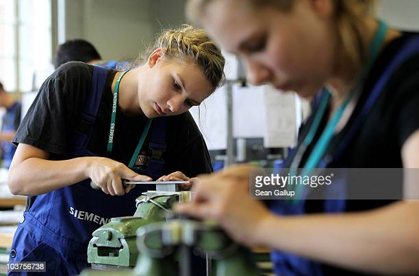 Female mechanical engineering trainees learn the basics of precision filing at the Siemens training center on September 1 2010 in Berlin Germany...
