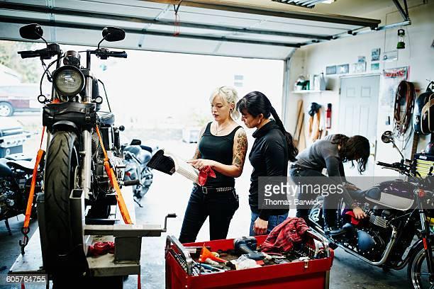Female mechanics referencing manual in garage