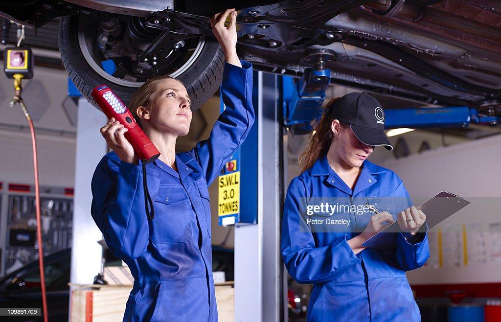 Female mechanics underneath car doing service : Stock Photo