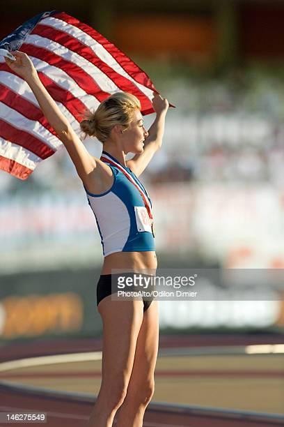 Female medalist holding up American flag