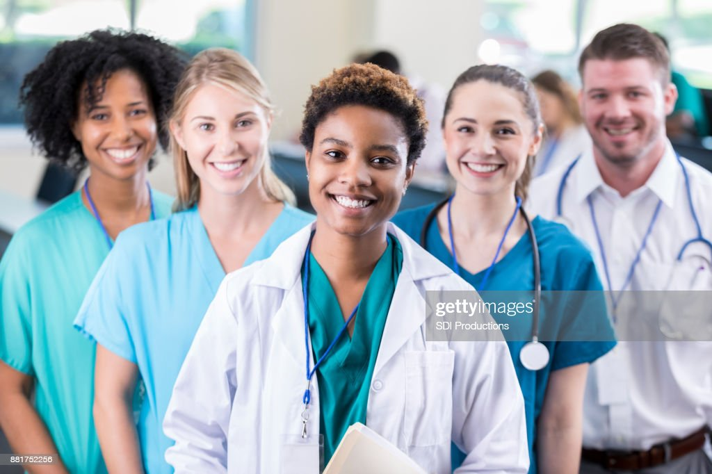 Female medical student poses with colleagues in lecture hall : Stock Photo
