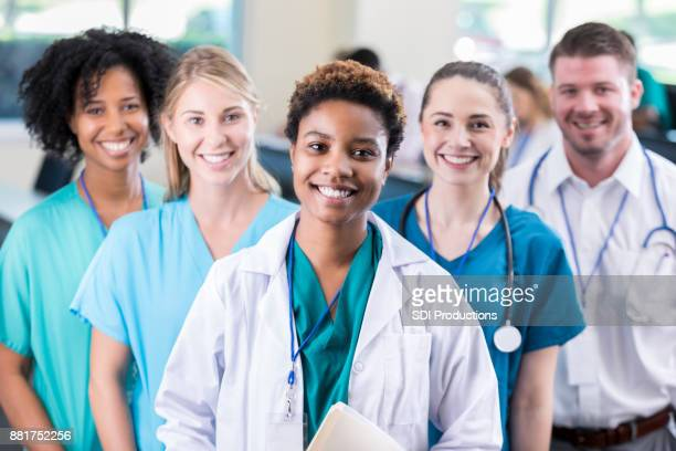 female medical student poses with colleagues in lecture hall - group of doctors stock pictures, royalty-free photos & images