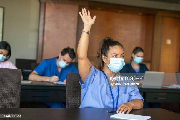 female medical student raising hand in class - australia stock pictures, royalty-free photos & images