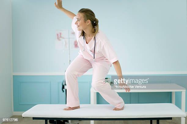 Female medical student standing on top of examination table, pretending to surf