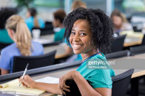 female medical student turns to smile for camera - medical student stock pictures, royalty-free photos & images