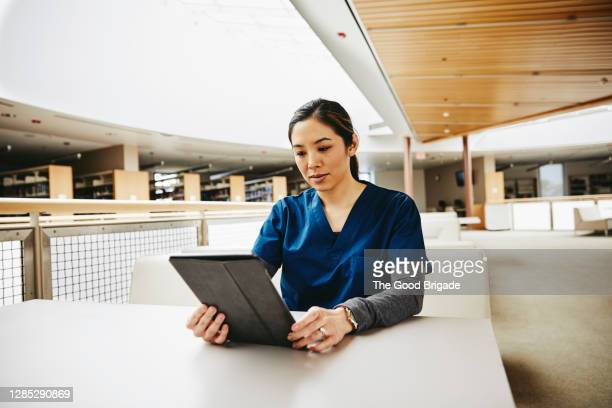 female medical student using digital tablet at table in library - education stock pictures, royalty-free photos & images