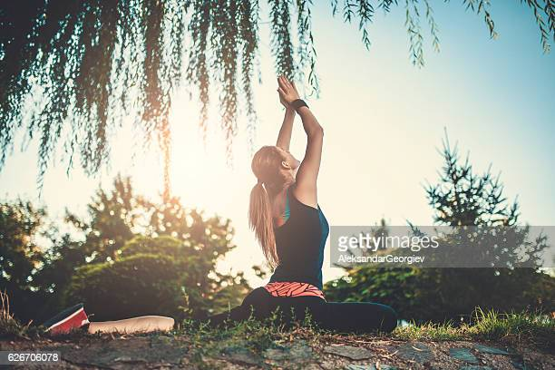 Female Meditating in Yoga Position with Raised Hands to Sunset